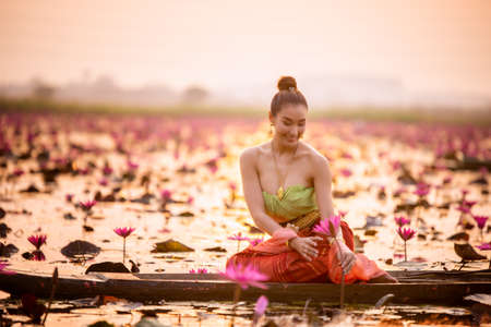 Young Asian women in Traditional dress in the boat and pink lotus flowers in the pond.Beautiful girls in traditional costume.Thai girl in traditional Thai northern traditional costume in lotus pond. Banco de Imagens
