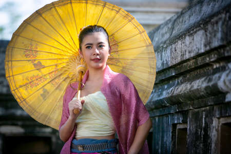 Portrait of an Smiling Young Woman in Thai Lanna Traditional Clothes are Smiling Young Woman Holding Flower Basket and and hold umbrella Against Thailand Temple