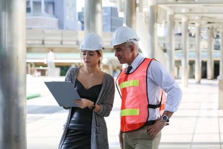Female industrial engineer wearing a white helmet while standing in a construction site with businessman talking on working plan, Engineer and architects at construction site concept 版權商用圖片