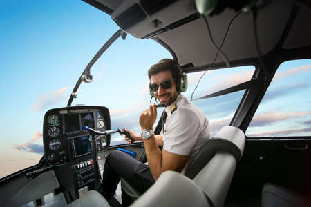 Shot of a mature Helicopter pilot using a headset while traveling in a helicopter, Business people traveling by helicopter Banque d'images