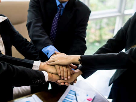 Diverse business people group put hands together in stack pile at training as concept of. Business people shaking hands, finishing up a papers signing. Meeting, contract and lawyer consulting concept.