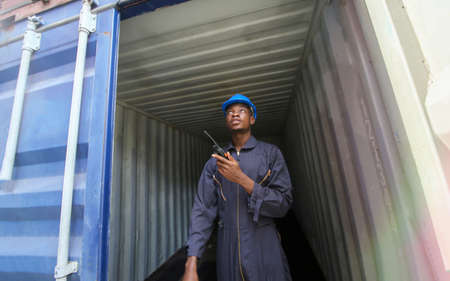 Engineer or supervisor checking and control loading Containers box from Cargo at harbor.Foreman control Industrial Container Cargo freight ship at industry.Transportation and logistic concept.