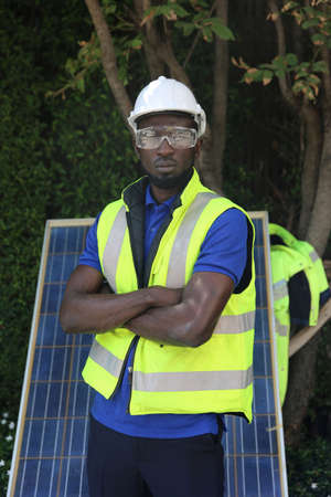 maintenance engineer, Solar energy systems engineer perform analysis solar panels, Portrait of engineer man or worker, people, with solar panels or solar cells on the roof in farm. Power plant with green field, renewable energy source in American. Eco technology for electric power. Stock fotó