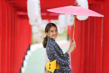 woman in kimono holding umbrella walking into at the shrine red gate, in Japanese garden.