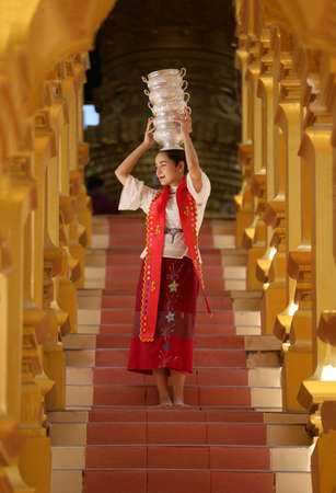 Young girl with traditional Burmese holding bowl of rice on the hand at beautiful golden pagoda in Myanmar
