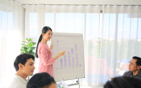Female coach or presenter talk interact with multiracial colleagues at meeting, happy young woman tutor make flip chart whiteboard presentation at office briefing