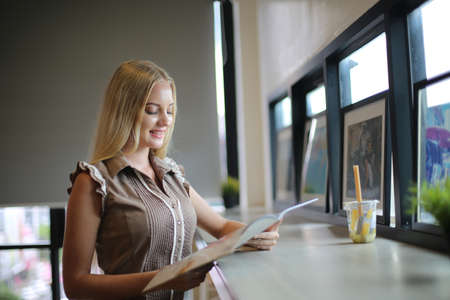 The side view of a young woman resting at the workspace at a cafe indoors. Stock fotó