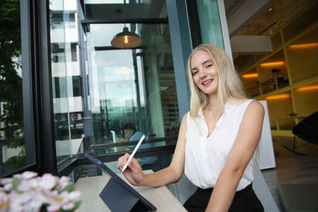 Young and cheerful woman working on digital tablet using wireless internet while sitting relaxed at cafe. Concept of leisure, freelance and mobile work Stock fotó