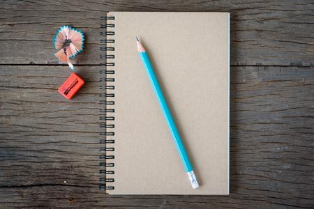 directorio telefonico: Un cuaderno abierto con el l�piz, naranja y sacapuntas en mesa de madera vieja.