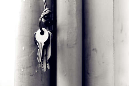 A string of keys hanging on the wall with a rope