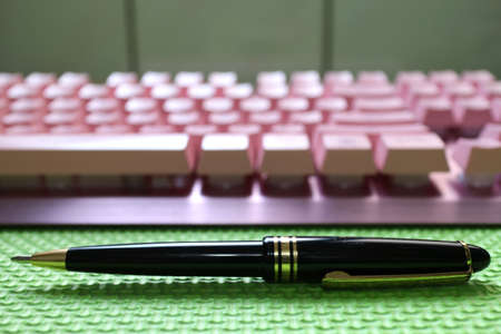 A black ballpoint pen, arranged with a pink computer keyboard, flat on a green background. Symbolize the new era and the changes and progress of the old era.