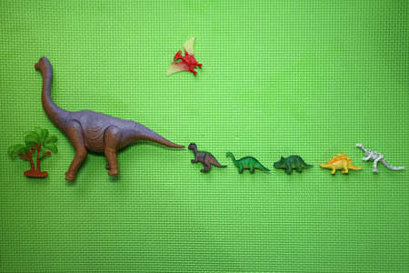 Dinosaur toys, from large to small, arranged in order, and a small palm tree, flat on a green background, children like it. Stock Photo