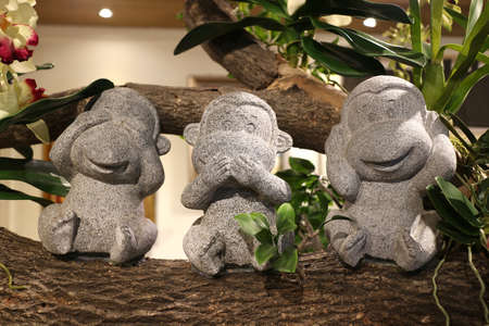Three stone sculpture of the monkey, sitting in the tree, the performance can not be seen, can not hear, can not say, a symbol of non-polite thing, you can not just look, listen, into the hexagram. Asian yellow kind of behavior. Stock Photo