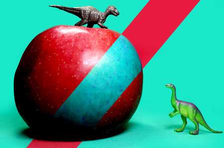 Fresh organic red apple with two dinosaur toys, flat lay on a turquoise background. Symbol of health, fun, sweet, juicy, to attract children.