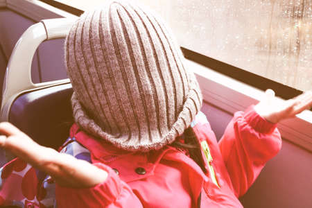 Children wearing brown wool hat, funny posture in the bus, while is raining outside.