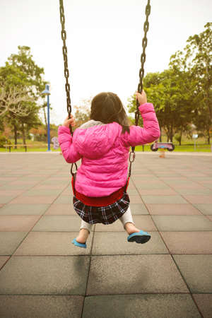 The little girl is playing on the swing in the park. Symbol of fun, childhood, happiness, dreams.