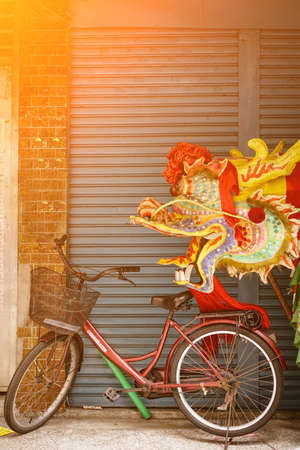Chinese dragon's head and bicycle. Dragon dance in China. Concept of blessing, pray, auspiciousness, happiness, and New Year. Stock Photo