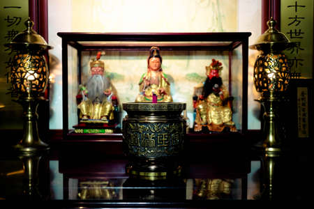 Buddha statue carved of wood.Incense burner.Worship God in Asian countries.The Chinese characters in the photo mean a lot of longevity, wealth, and luck.