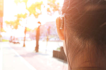 Hearing loss child wearing a hearing aid.At the bus stop.