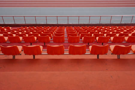 A lot of orange chairs in the stadium.