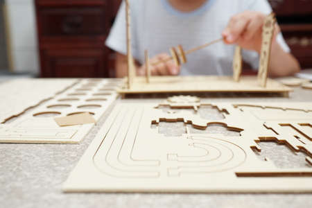 A child playing with 3d wooden puzzle. Parts include gears, rails. Foto de archivo - 150551736
