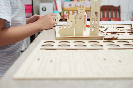 A child playing with 3d wooden puzzle. Parts include gears, rails. Foto de archivo - 150551748