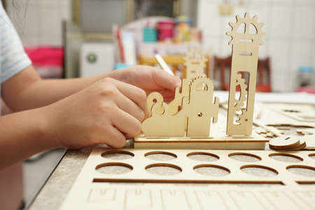 A child playing with 3d wooden puzzle. Parts include gears, rails. Foto de archivo - 150551752