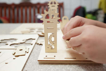A child playing with 3d wooden puzzle. Parts include gears, rails. Foto de archivo - 150551765