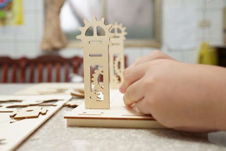 A child playing with 3d wooden puzzle. Parts include gears, rails. Foto de archivo - 150551795