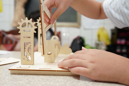 A child playing with 3d wooden puzzle. Parts include gears, rails. Foto de archivo - 150551797