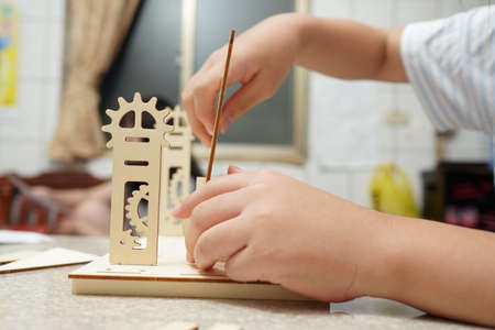 A child playing with 3d wooden puzzle. Parts include gears, rails. Foto de archivo - 150551798