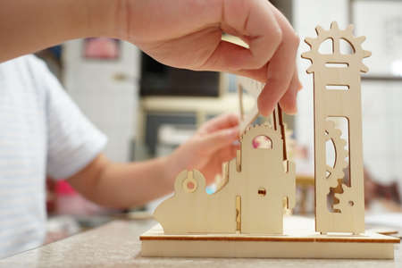 A child playing with 3d wooden puzzle. Parts include gears, rails. Foto de archivo - 150551799