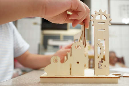 A child playing with 3d wooden puzzle. Parts include gears, rails. Foto de archivo - 150551800