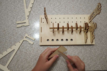 A child playing with 3d wooden puzzle. Parts include gears, rails. Foto de archivo - 150551803