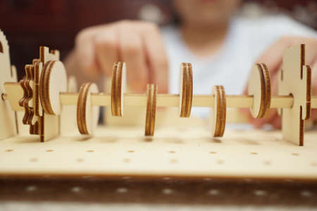 A child playing with 3d wooden puzzle. Parts include gears, rails.
