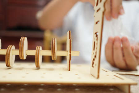 A child playing with 3d wooden puzzle. Parts include gears, rails. Foto de archivo - 150551811