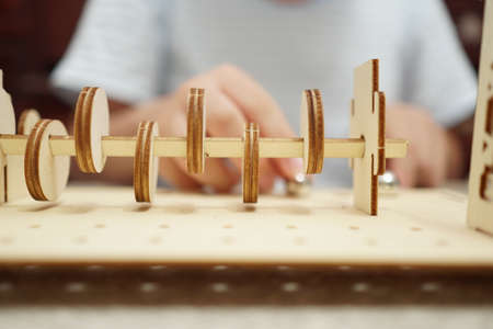 A child playing with 3d wooden puzzle. Parts include gears, rails. Foto de archivo - 150551813