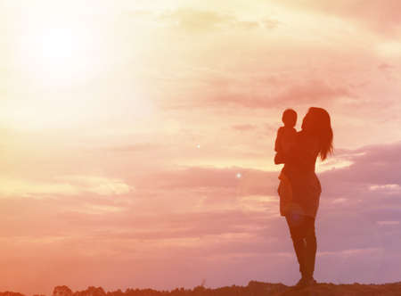 encouraged: Mother encouraged her son outdoors at sunset, silhouette concept