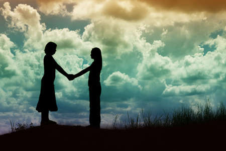 facing each other: silhouette of two girls facing each other hold hands together