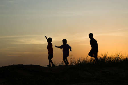children hands: silhouette of a happy children and happy time sunset