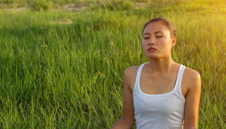 breathe easy: Yoga in the city: beautiful young fit woman wearing sportswear meditating, breathing, sitting with crossed legs in Half Lotus Posture on the street on summer day, Ardha Padmasana, copy space Stock Photo
