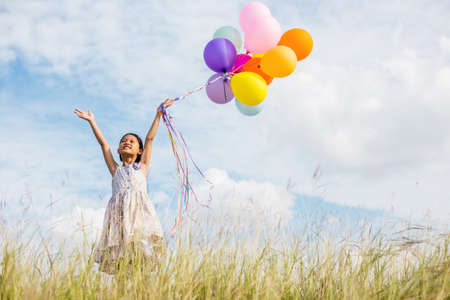 Cute little girl holding colorful balloons in the meadow against blue sky and clouds,spreading hands. Stock Photo