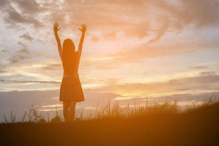 trust god: Silhouette of woman praying over beautiful sky background