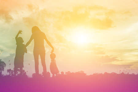 coming home: a silhouette of a happy young girl child the arms of his loving mother for a hug, in front of the sunset in the sky on a summer day.