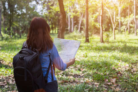 Women hiker with backpack checks map to find directions in wilderness area Stock Photo
