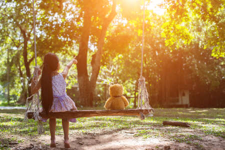 A little girl and teddy bear sitting on a swing.