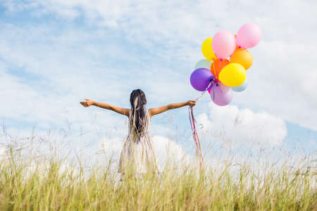 Cute little girl holding colorful balloons, running in the meadow against blue sky and clouds.