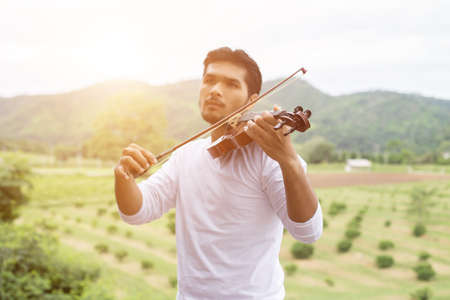 Young hipster musician man playing violin in the nature outdoor lifestyle behind mountain. Stock Photo
