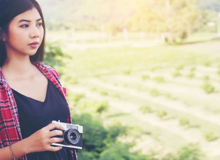 Vintage of beautiful women photography standing hand holding retro camera with sunrise,dream soft style
