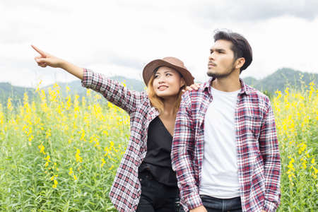 Young hipster couple relaxing in yellow flower field at summer. Enjoying with nature.